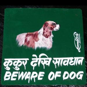 Folk art beware of Spaniel sign hand painted on metal by Nepali signboard artist