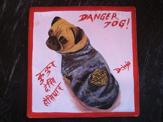 Folk art portrait of Taco the Pug dressed in his Harley Davidson jacket, hand painted on metal in Nepal