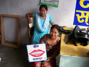 Arjun Karki's staff with a dentist sign hand painted on metal in Nepal