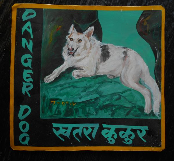 Folk art portrait of a white German Shepherd dog hand painted on metal in Nepal.