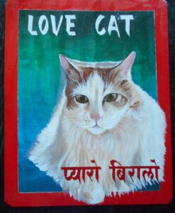 Folk art portrait of white long-haired domestic cat hand painted on metal in Nepal