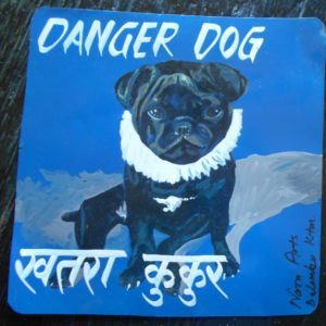 Folk art portrait of a black Pug dog, hand painted on metal in Nepal