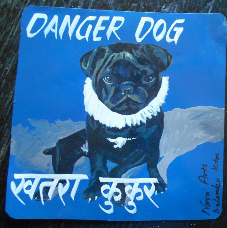 Folk art portrait of a black Pug dog, hand painted on metal in Nepal