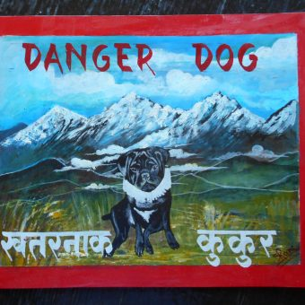 Folk art portrait of a black Pug set against the backdrop of the Himalayas, hand painted on metal